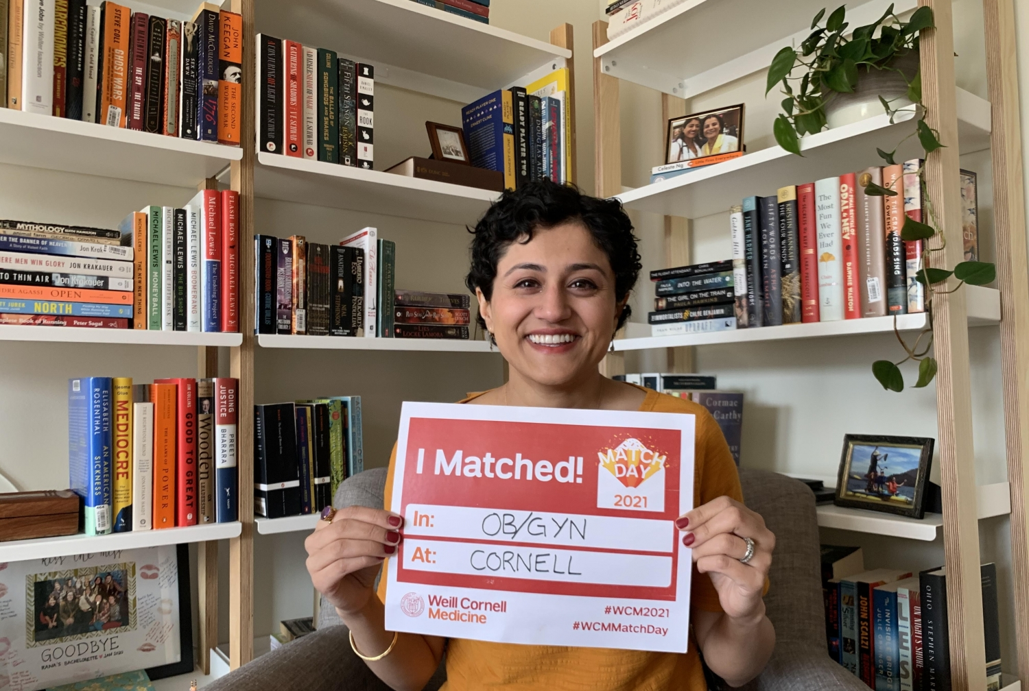 a woman smiling for a photo, holding a sign showing where she matched for Match Day 2021