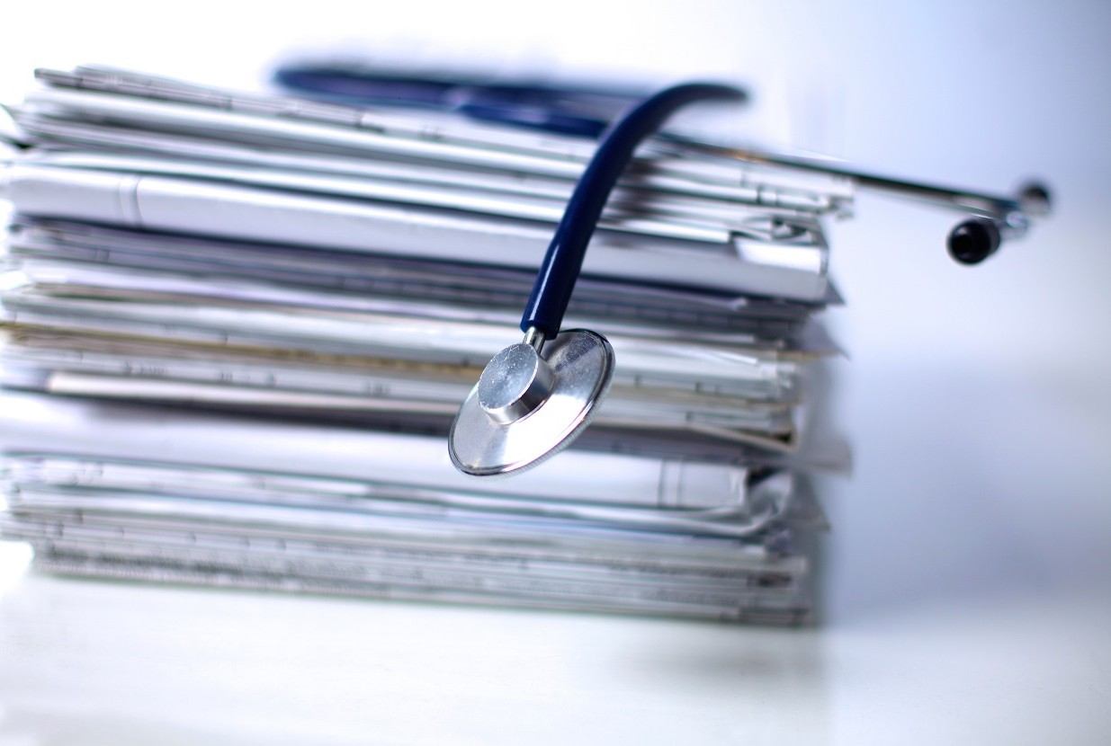 Medical stethoscope on a stack of paper.